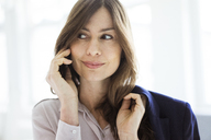 Portrait of smiling businesswoman on cell phone - MOEF00844
