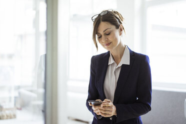 Businesswoman using cell phone in bright room - MOEF00847