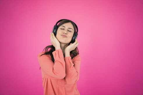 Woman in front of pink wall listening to music on headphones - MOEF00853