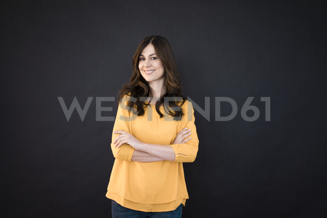 Portrait of smiling woman in front of black wall - MOEF00856