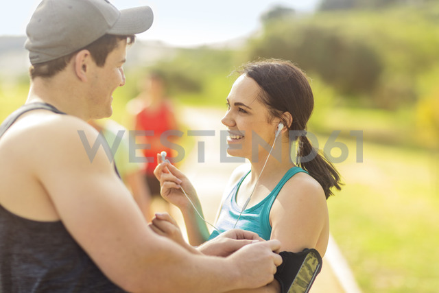 Smiling young man and woman preparing to run - ZEF15002