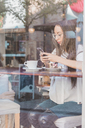 Woman with cake checking her cell phone in a cafe - AFVF00004