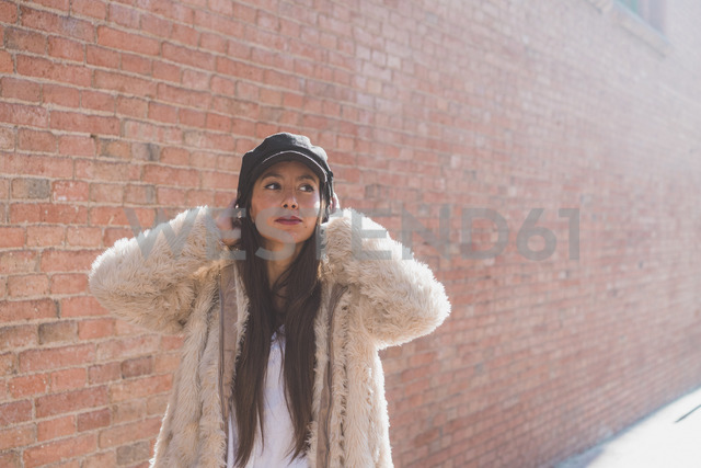 Stylish young woman in front of brick wall - AFVF00007