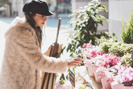 Stylish young woman buying flowers in the city - AFVF00010