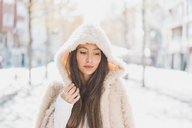 Portrait of young woman wearing hooded fur jacket - AFVF00016