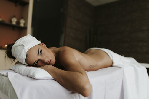 Portrait of young woman lying on lounge in a spa - OCAF00148