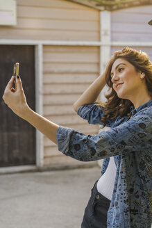 Smiling young woman taking selfie with cell phone - AFVF00029