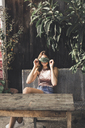 Young woman sitting on a bench outdoors covering eyes with a leaf - AFVF00032