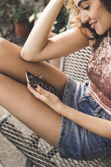 Smiling young woman sitting on bench using cell phone - AFVF00041