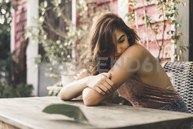 Portrait of young woman sitting on bench outdoors - AFVF00044