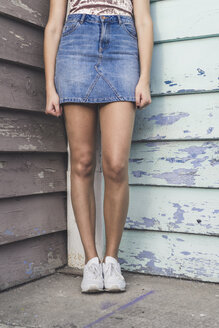 Young woman standing in a corner wearing denim skirt, partial view - AFVF00050
