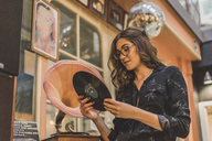 Portrait of smiling young woman standing in front of antique shop looking at gramophone record - AFVF00053