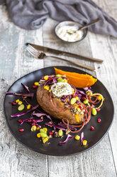 Kumpir, filled sweet potatoe, red cabbage, corn, edamame, carrots, quinoa, creme fraiche on plate - SARF03584