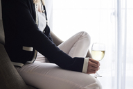 Close-up of woman having a glass of wine at home sitting in armchair - IGGF00403