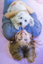 Portrait of happy woman lying on bed with her dog - AFVF00072