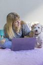 Woman with laptop sitting on bed  stroking her dog - AFVF00075