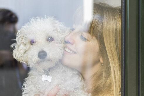 Happy woman behind windowpane cuddling her dog - AFVF00087