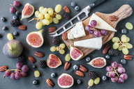 Plate with cheese, figs, grapes, blueberries, brambles, pecan nuts, chopping board, knife - SARF03587