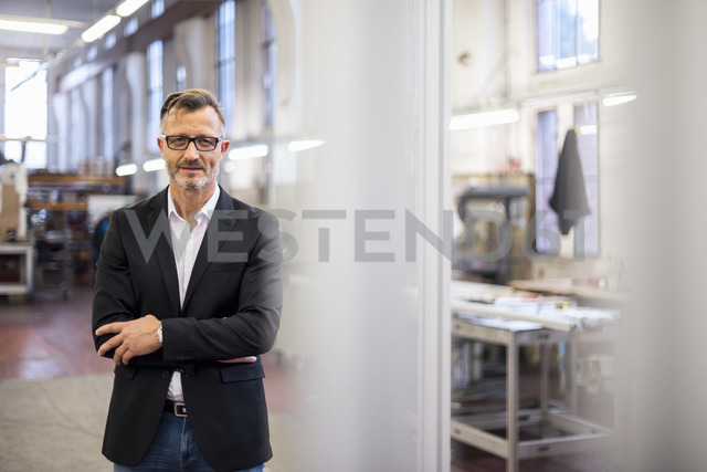 Portrait of smiling mature businessman in factory - DIGF03332