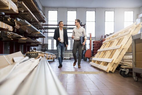 Two businessmen walking and talking in factory storeroom - DIGF03338