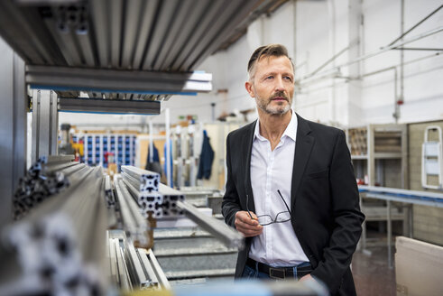 Mature businessman in factory thinking - DIGF03344