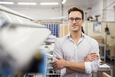 Portrait of smiling young businessman in factory - DIGF03347