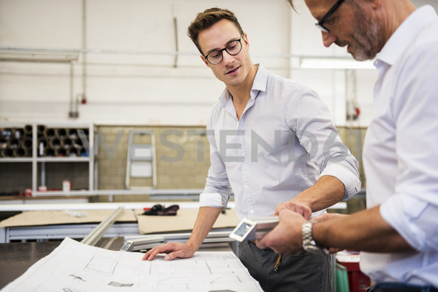Two businessmen in factory discussing component and plan - DIGF03350