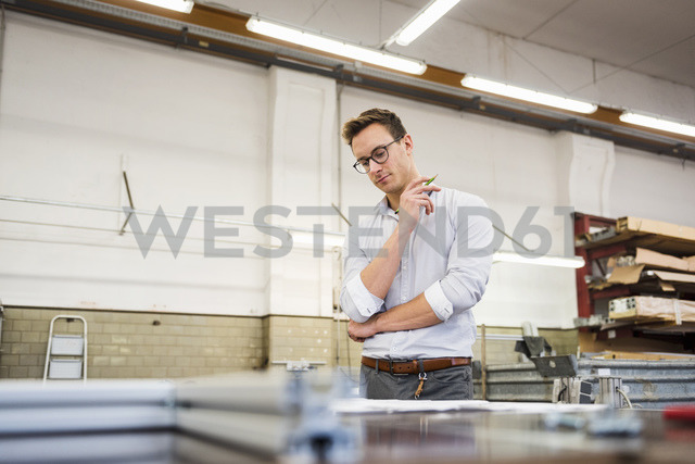 Young businessman in factory working on plan - DIGF03356