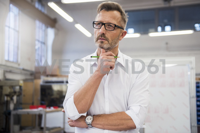 Mature businessman in factory thinking - DIGF03359