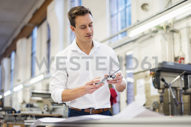Young businessman in factory holding component - DIGF03365