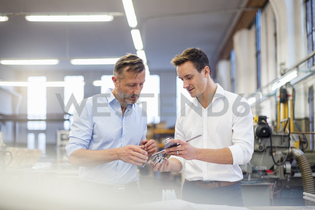 Two businessmen in factory discussing product - DIGF03368