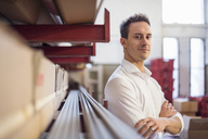 Portrait of confident young businessman in factory storeroom - DIGF03371