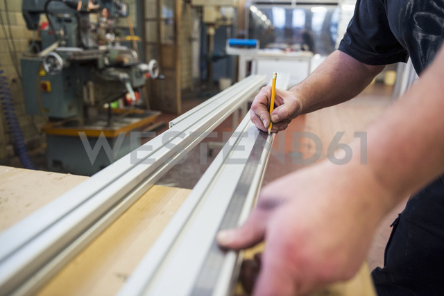 Close-up of man in factory working on metal component - DIGF03383