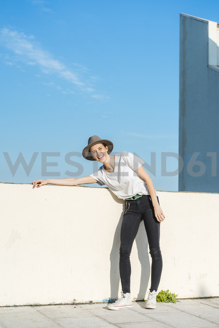 Portrait of laughing woman wearing hat leaning on wall - AFVF00105