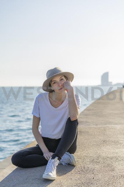 Spain, Barcelona, portrait of woman wearing hat sitting at waterfront promenade - AFVF00108