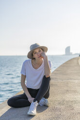 Spain, Barcelona, portrait of woman wearing hat sitting at waterfront promenade - AFVF00108