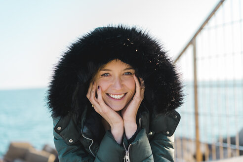 Portrait of happy woman with head in her hands wearing hooded jacket - AFVF00111