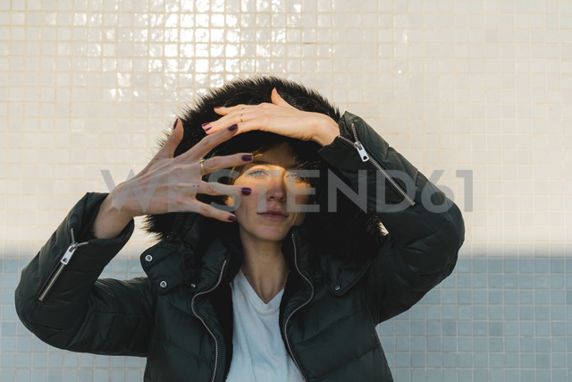 Portrait of woman wearing hooded jacket in front of tiled wall - AFVF00114