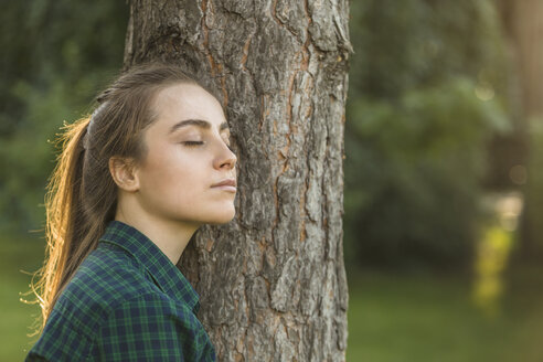 Beautiful woman with eyes closed leaning on tree trunk at park - FSIF01396