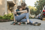 Happy young couple embracing while sitting on skateboard outdoors - FSIF01399