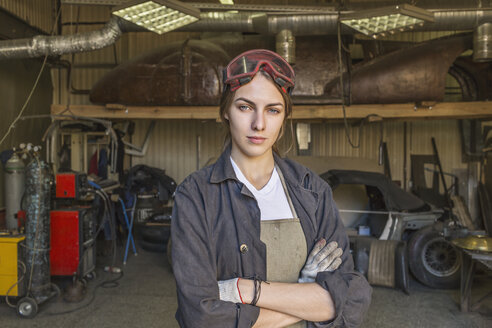 Portrait of confident female mechanic with arms crossed at garage - FSIF01414