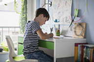 Side view of boy doing homework at table in house - FSIF01417