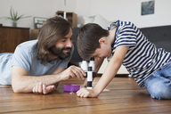 Father and son using microscope on hardwood floor - FSIF01429