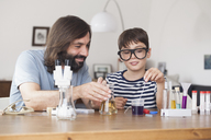 Father and son working on school science project at home - FSIF01432