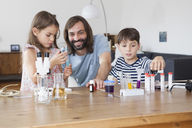 Father and children doing science experiment on table in house - FSIF01435