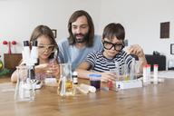 Father assisting children in doing school science project at home - FSIF01441
