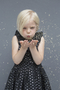 Girl blowing glitter against gray background - FSIF01462