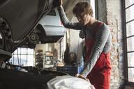 Mechanic examining car engine at garage - FSIF01465