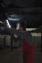 Mechanic holding illuminated fluorescent light while examining underneath car - FSIF01468