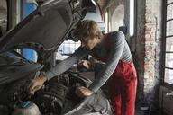 Mechanic examining car engine at auto repair shop - FSIF01471